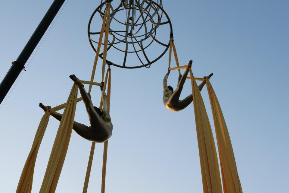 Two aerialists perform in mid-air from yellow ropes under a blue sky.
