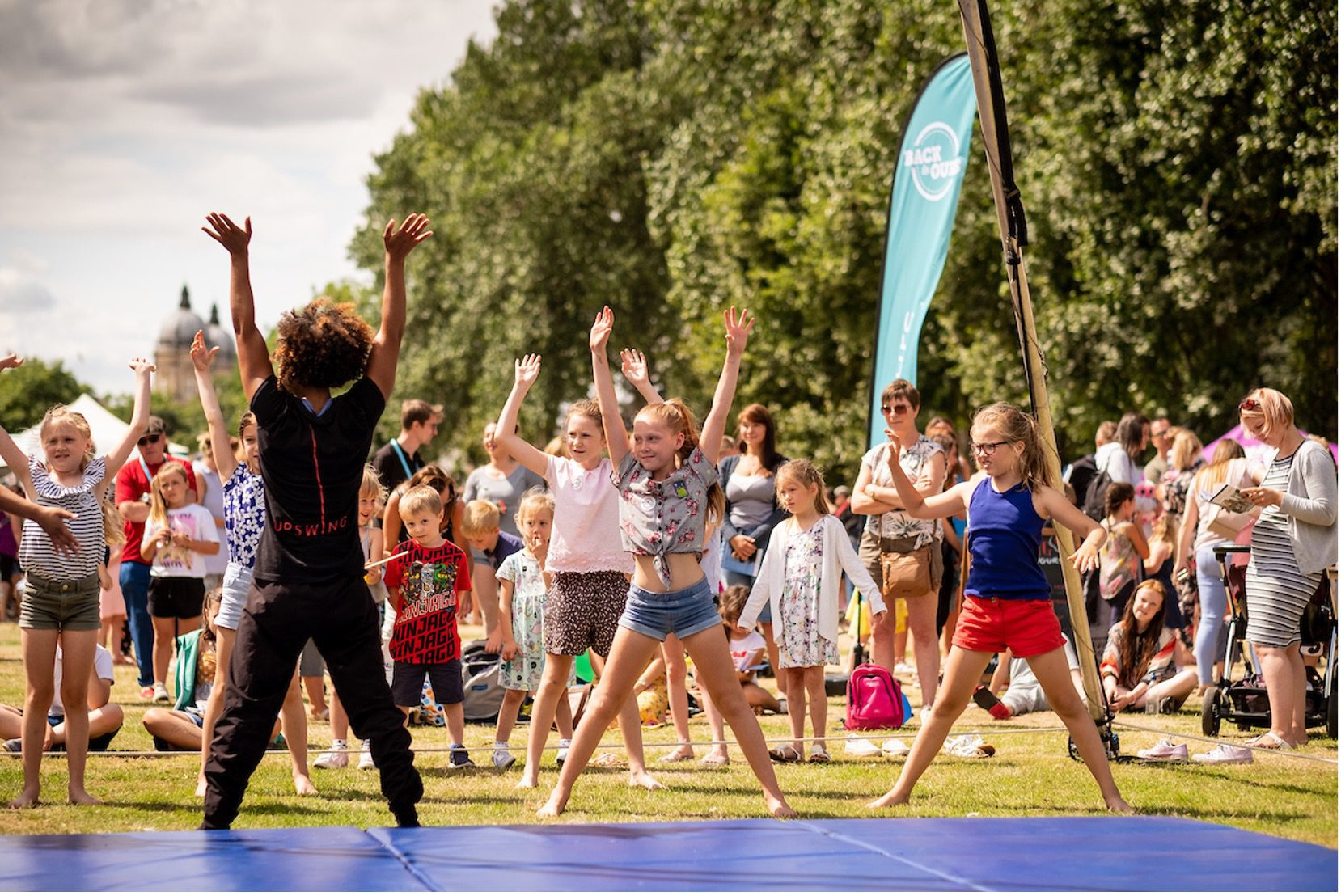 A group of children copy a dance routine from a workshop leader at a festival
