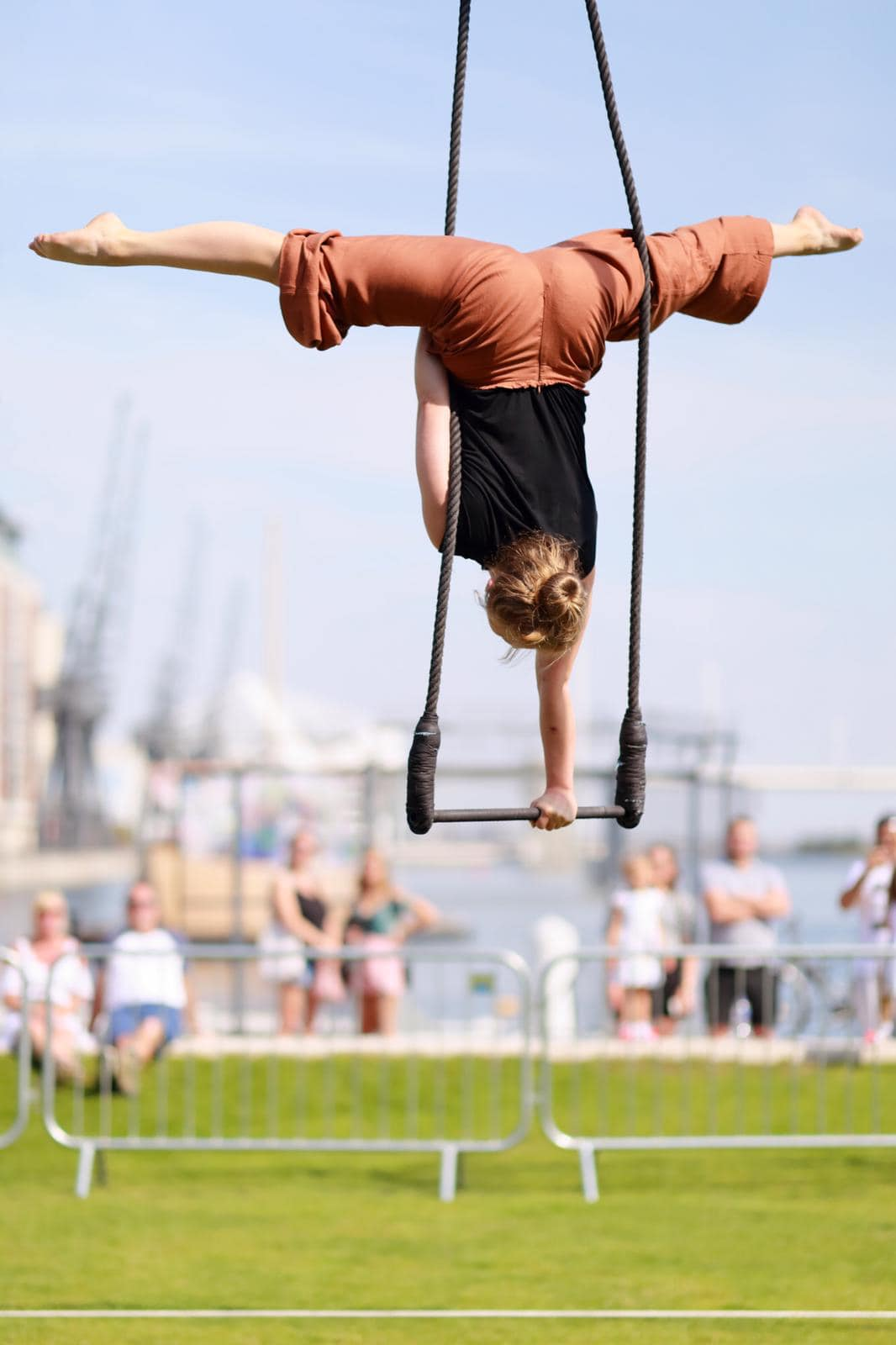A circus performer supports themselves on a trapeze and performs the splits in the air while an audience watches.