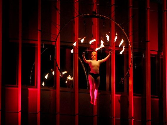 A woman holds fire poi above her head in a red-lit room.