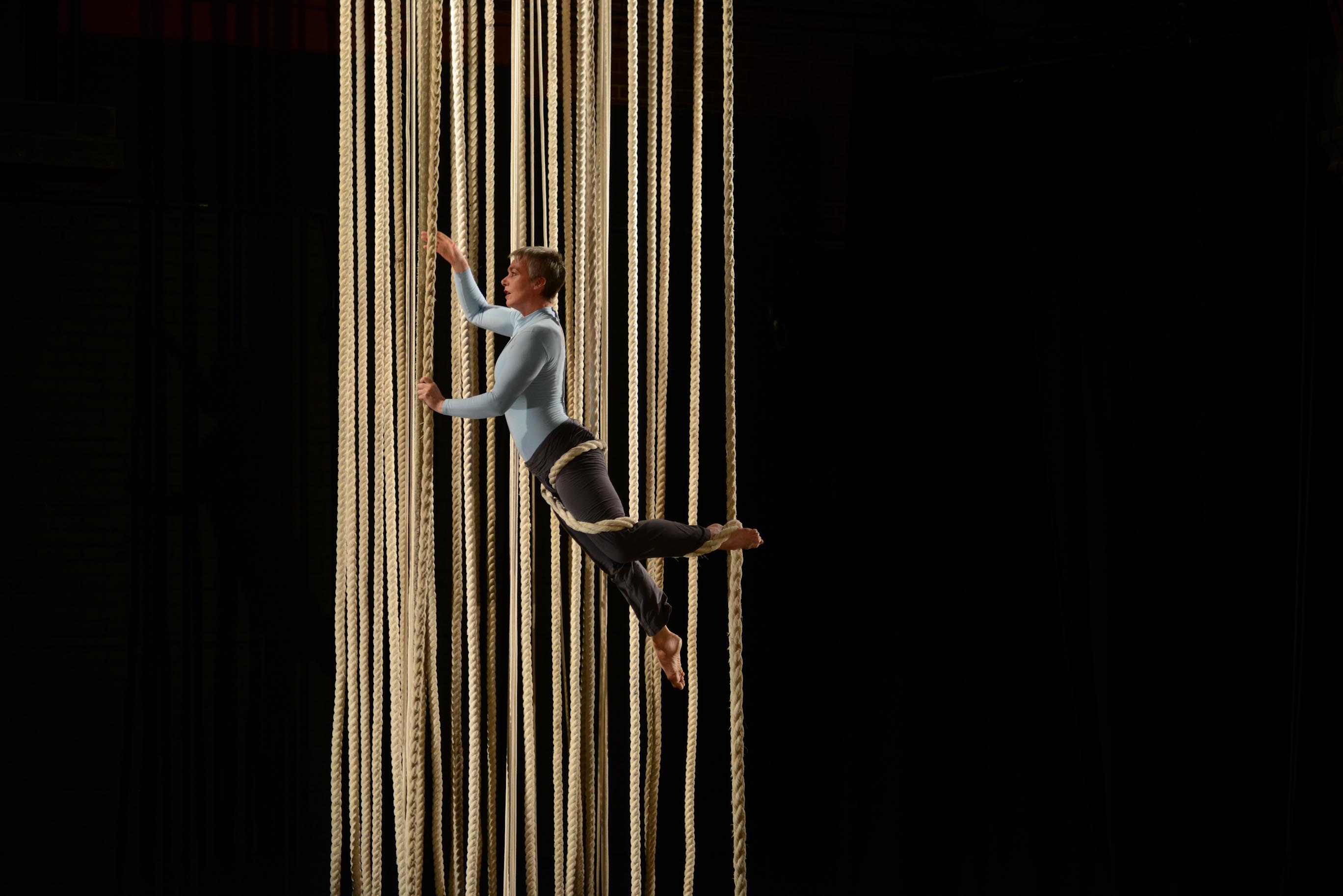 An aerialist in a dark room holds herself up whilst dangling in lots of ropes.