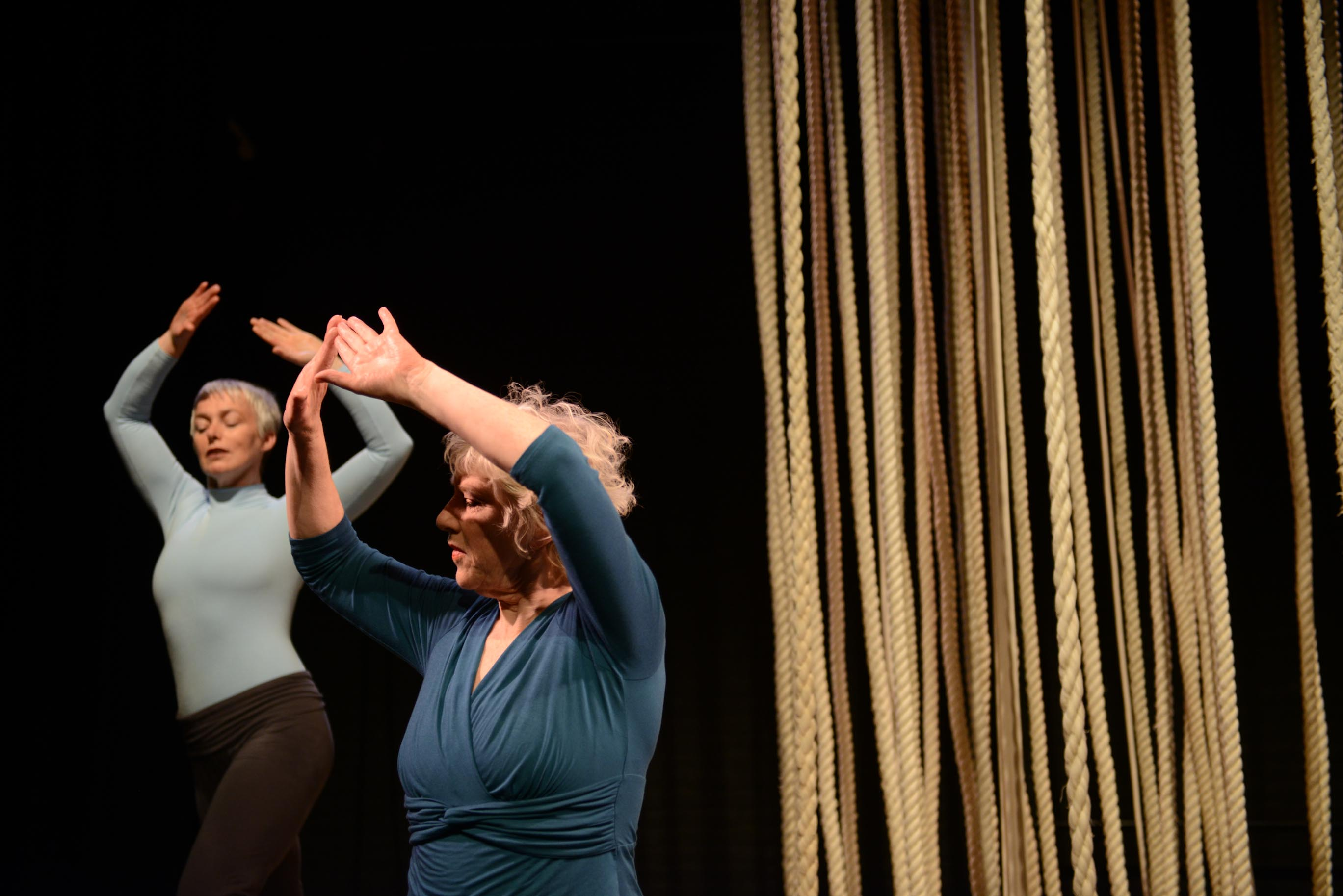 Two female dancers raise their arms in the air in a dark room filled with ropes.