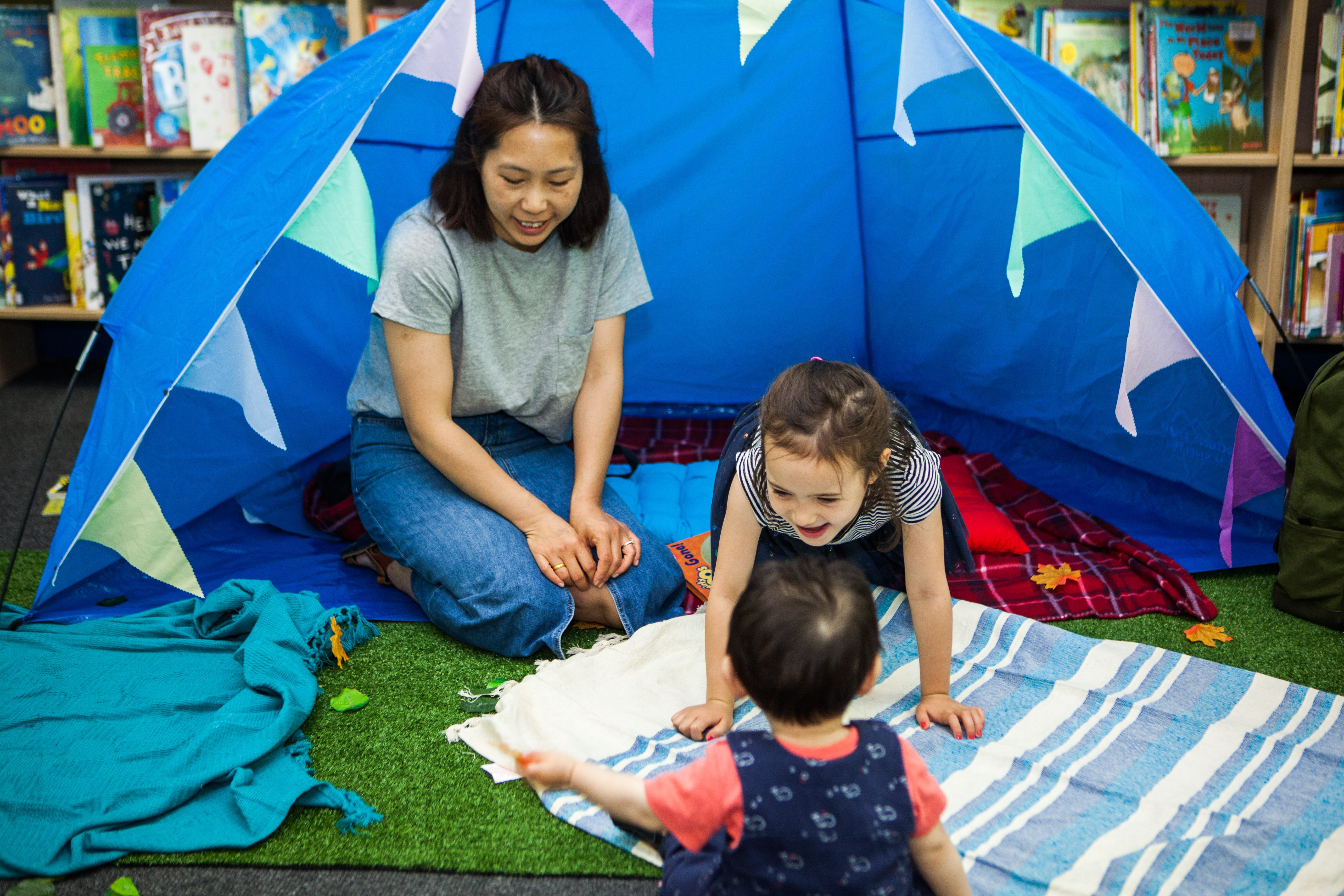A woman sits in a blue tent, inside a library, watching two children play on a rug.