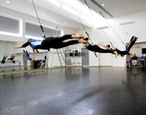 Three people jump forwards in a dance studio, whilst attached to bungee ropes.