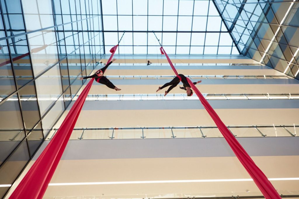 Two aerialists dangle from red ropes high inside a building.