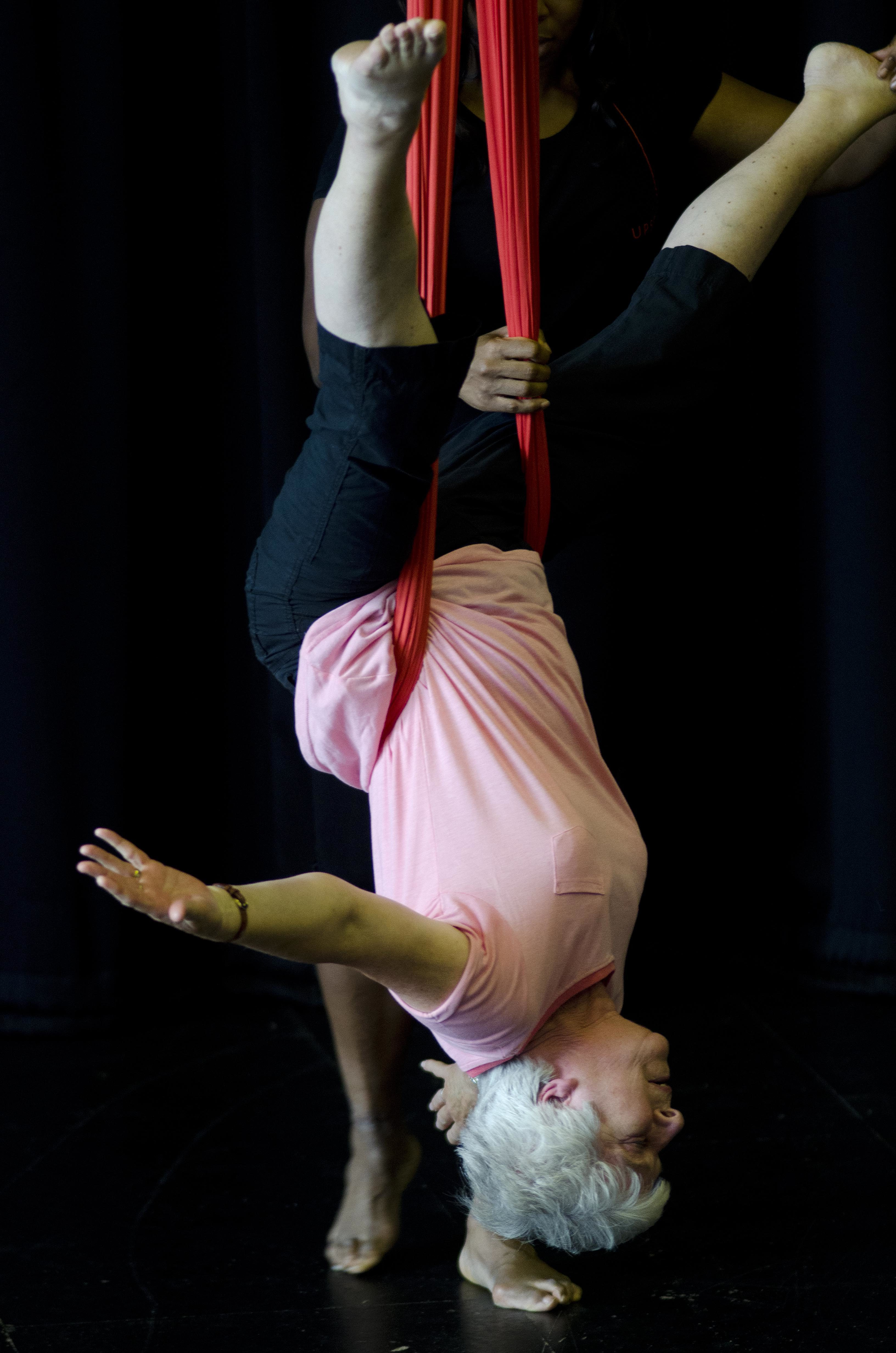 An older woman is held up on silk ropes upside down.