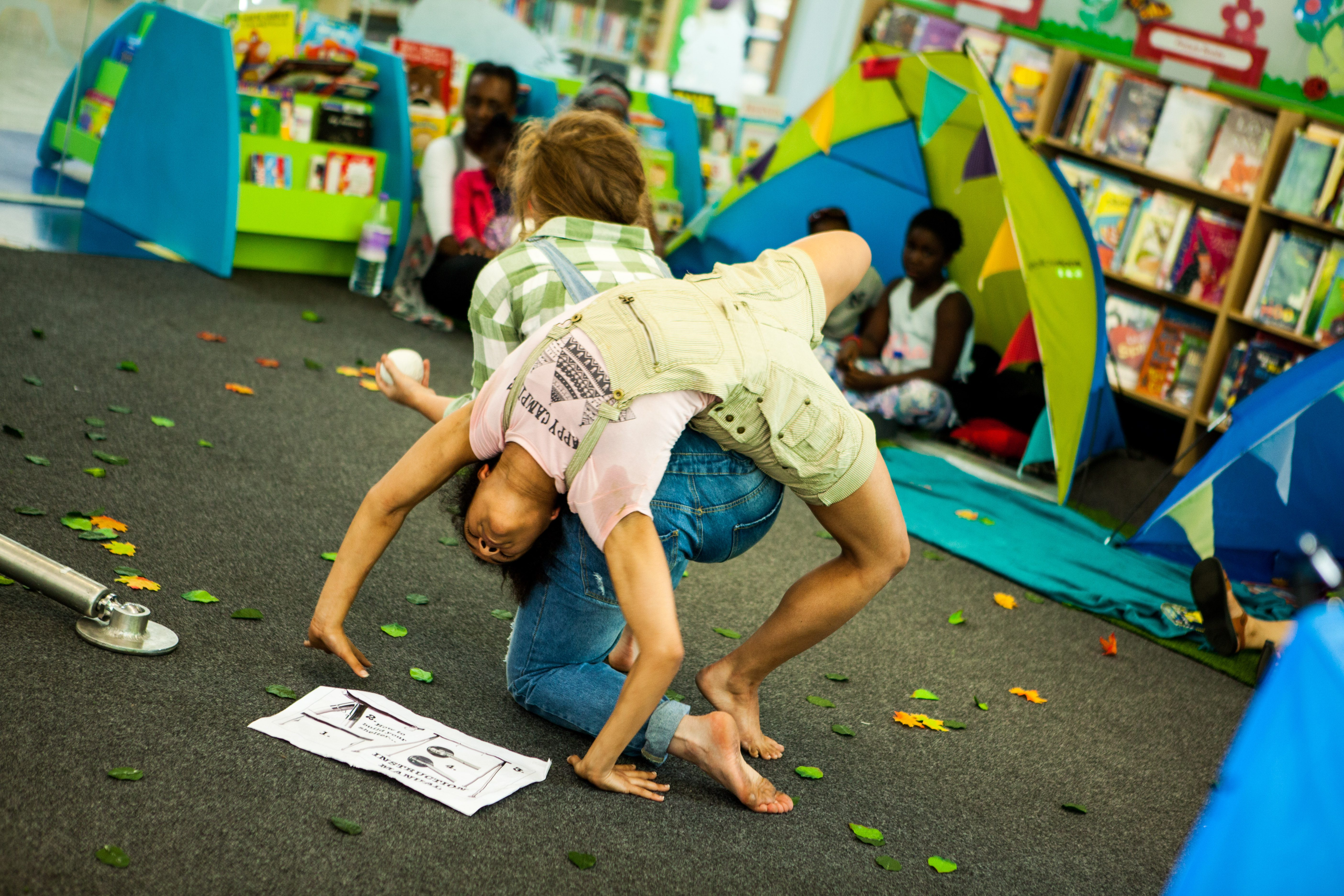One female dancers does a crab move over another in a brightly colours library with children watching.
