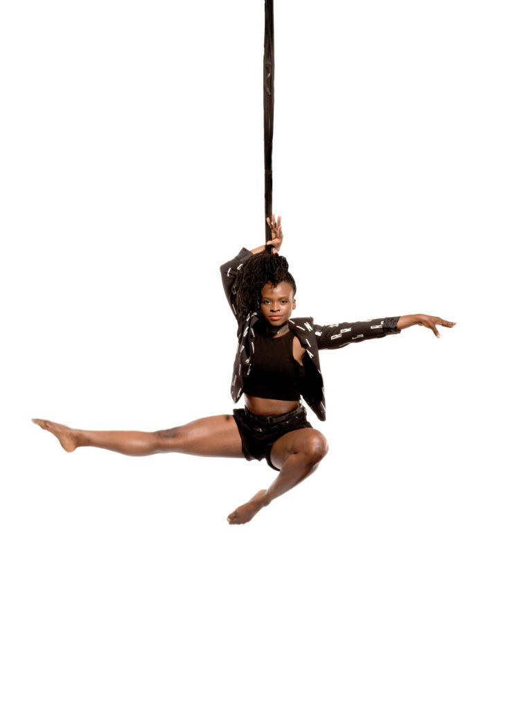 An aerialist poses in the air attached to a bungee rope.