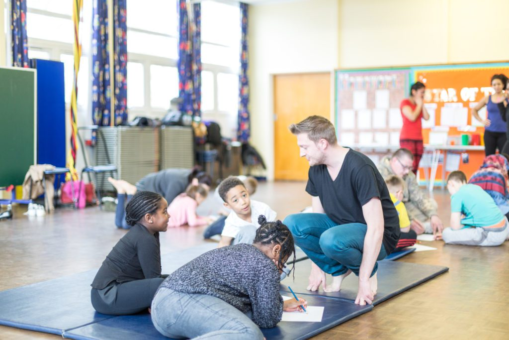 A man crouches down in a brightly decorated classroom full of children.