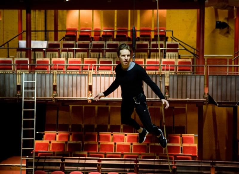 A male performer is suspended in the air in an empty theatre.