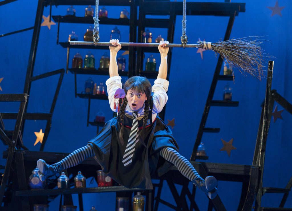 A performer dressed as a witch hangs from a broom-shaped trapeze on a blue stage.