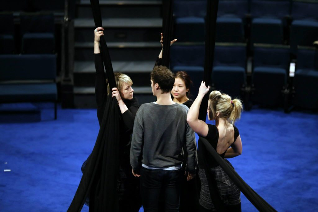 A group of performers stand in the middle of a blue stage in a circle. Some hold black aerial silks.