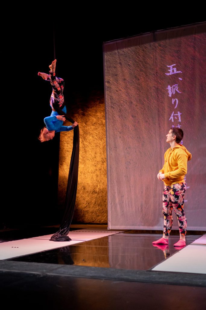 An aerialist hangs upside down from a rope, with another person standing and watching them.