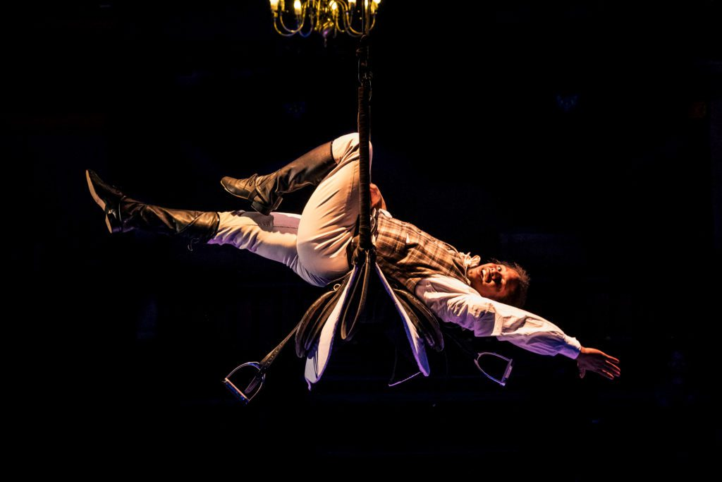 A performer dressed as a jockey lies back across a trapeze with their arms and legs pointed outwards.