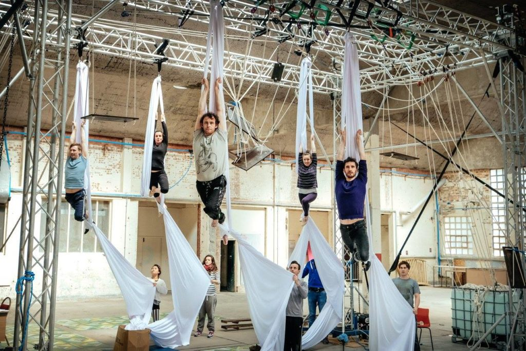 Five aerialists hang from silks while five people on the ground hold the ends of the fabric.