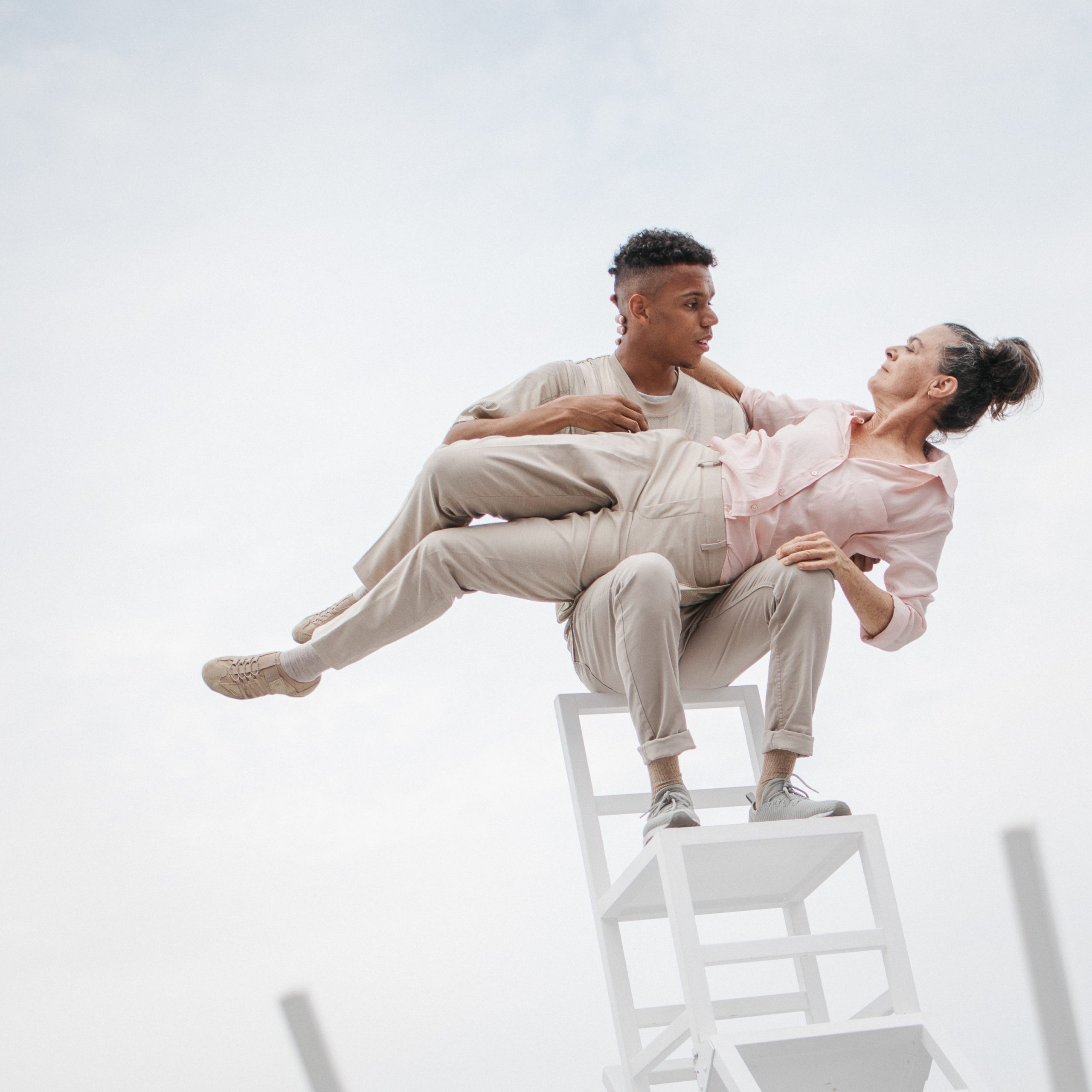 Two performers balance on a stack of chairs holding each other.
