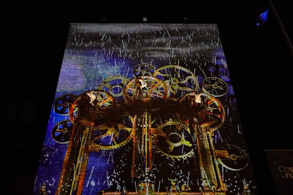 Aerial performers hang on the side of a building that has a large projection of cogs on it.