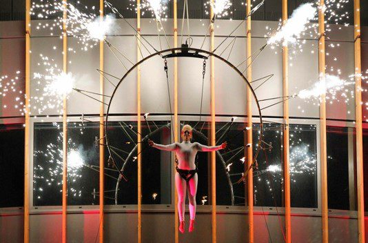 A person is suspended from a pyrotechnics costume that shoots fireworks all around them.