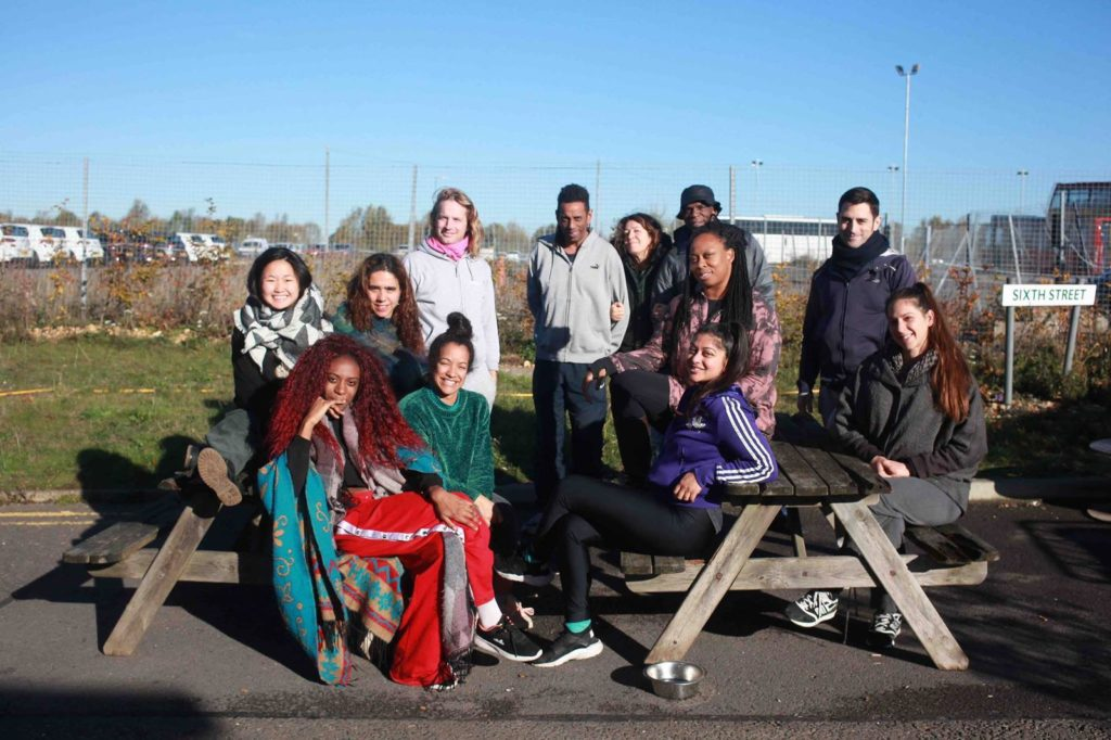 A diverse group of 12 people sit outside on picnic benches, smiling.