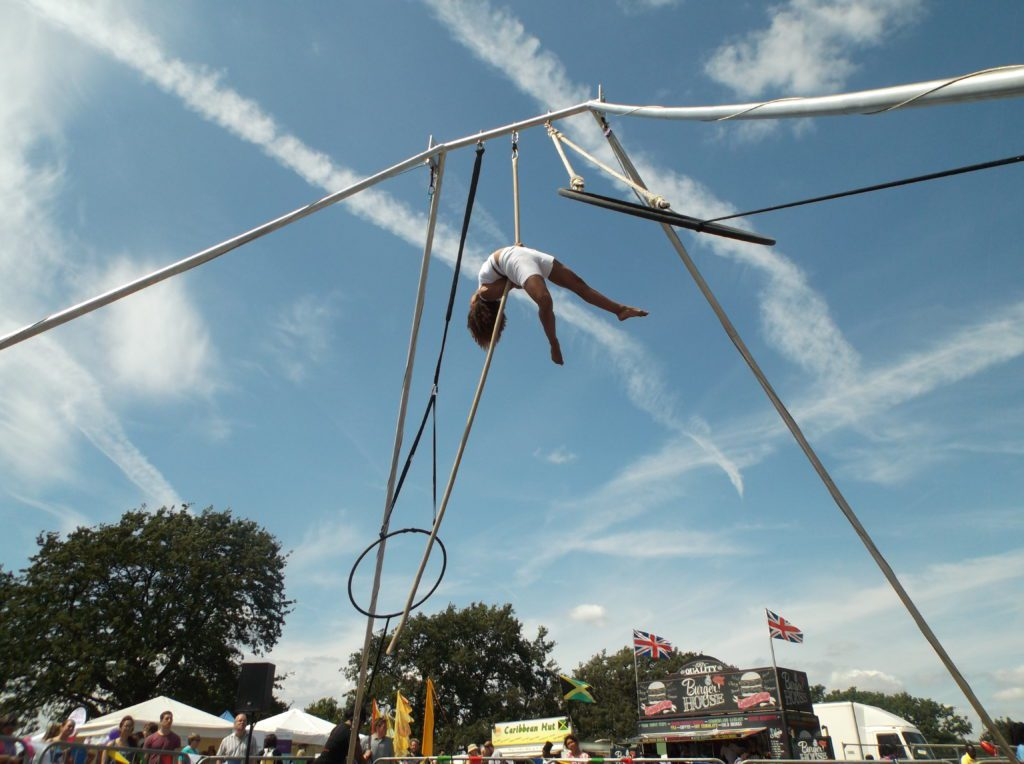 An Aerialist hangs from a rope, with a big blue sky behind them.