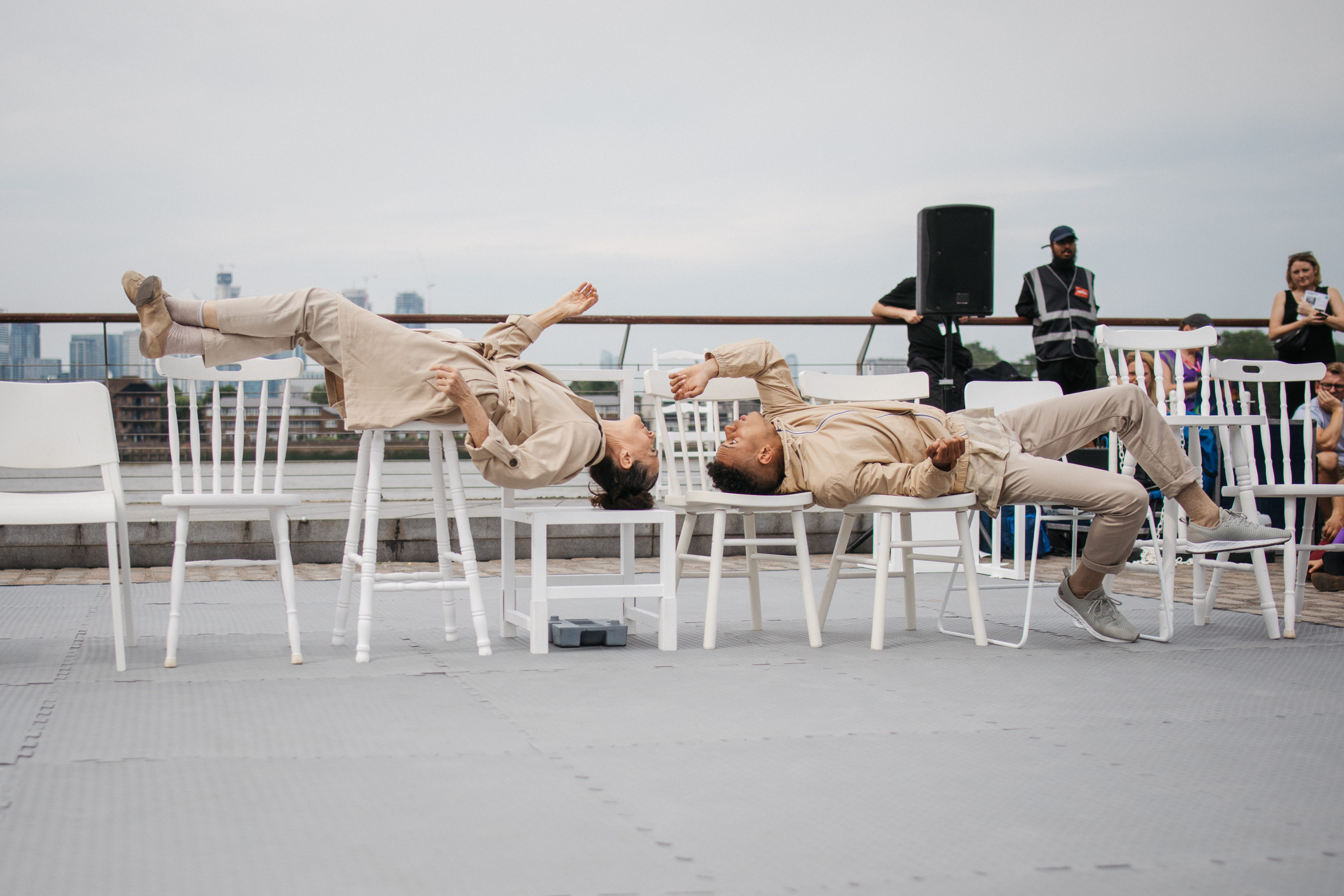 Two performers lie back on chairs and nearly touch hands.
