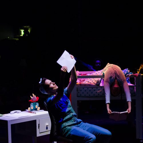 A woman holds up a piece of paper and looks at it in a dark room.