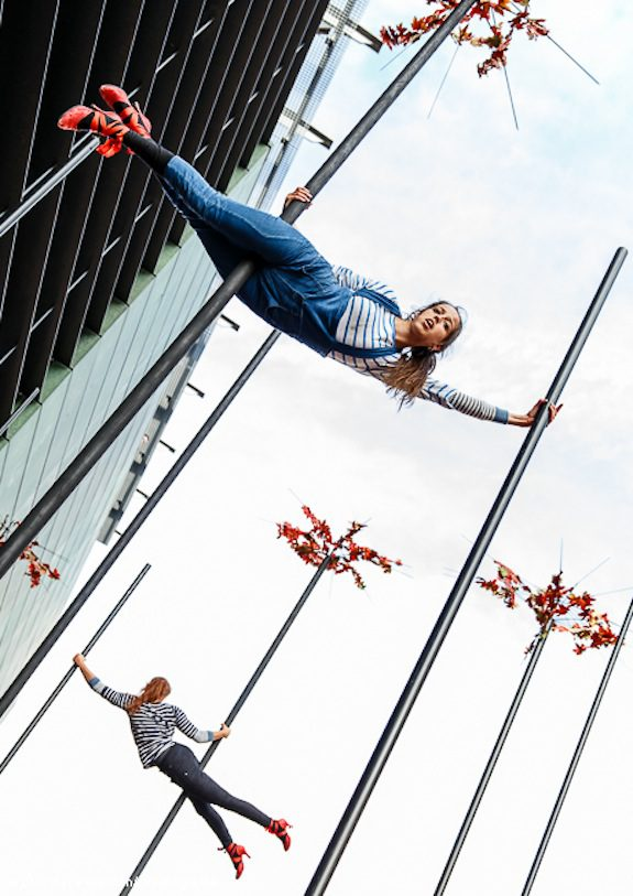 Two performers hold themselves up on chinese poles