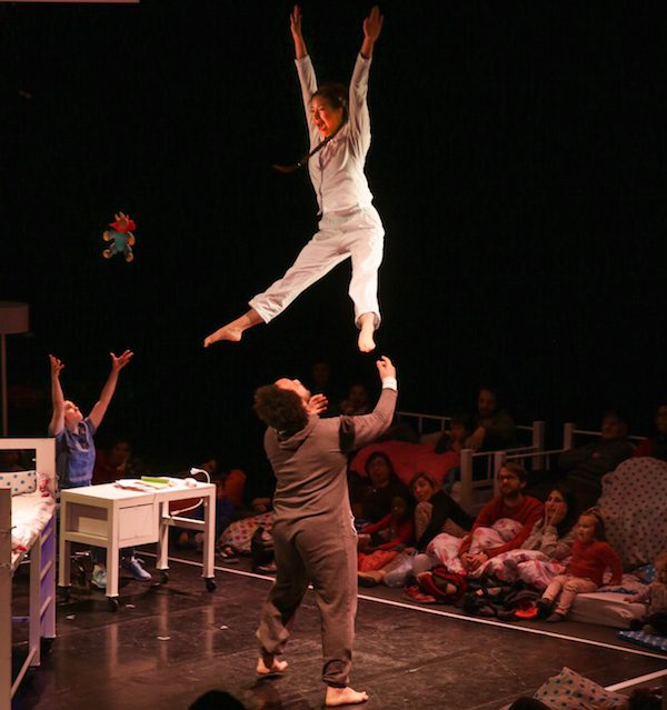 Three performers are on a dark stage with an audience sitting on the floor. A man throws and woman into the air.