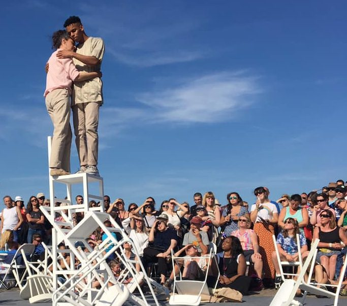 Two performers stand on a stack of chairs and hug, while a large audience watches.