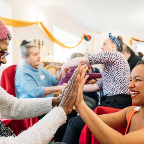 Two women clap hands and smile in a care home