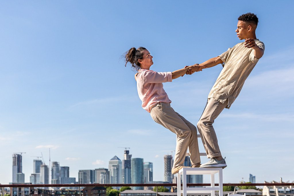 Two performers stand on a high chair. They hold each other's arms and balance, leaning backwards. A cityscape is behind them.