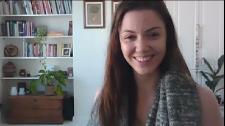 A woman smiling, with long brown hair, in front of a bookshelf.