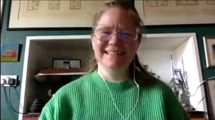 A woman smiling wearing a green jumper and glasses.