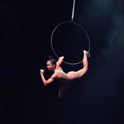 A female aerialist hangs from an aerial hoop in a black room