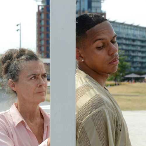 A caucasian female in her sixties and a black male in his twenties stand outside