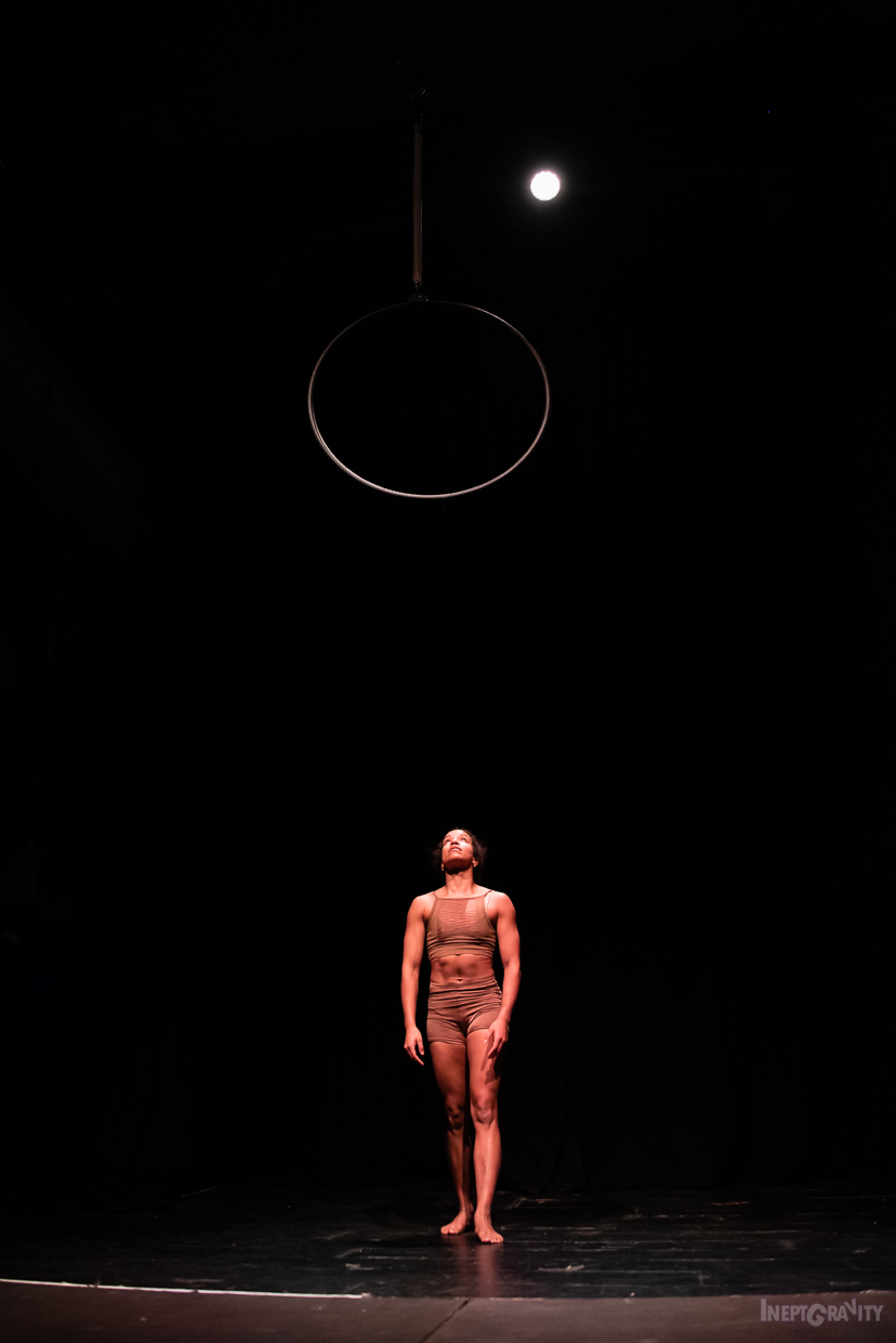 A woman stands in a dark room looking up at an aerial hoop.