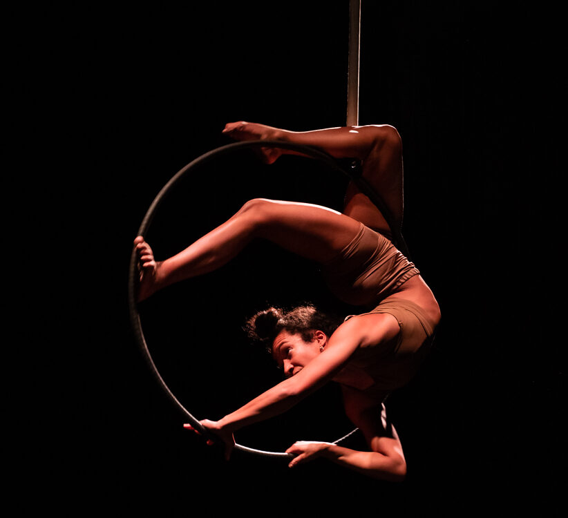 A woman bends her body and balances inside an aerial hoop