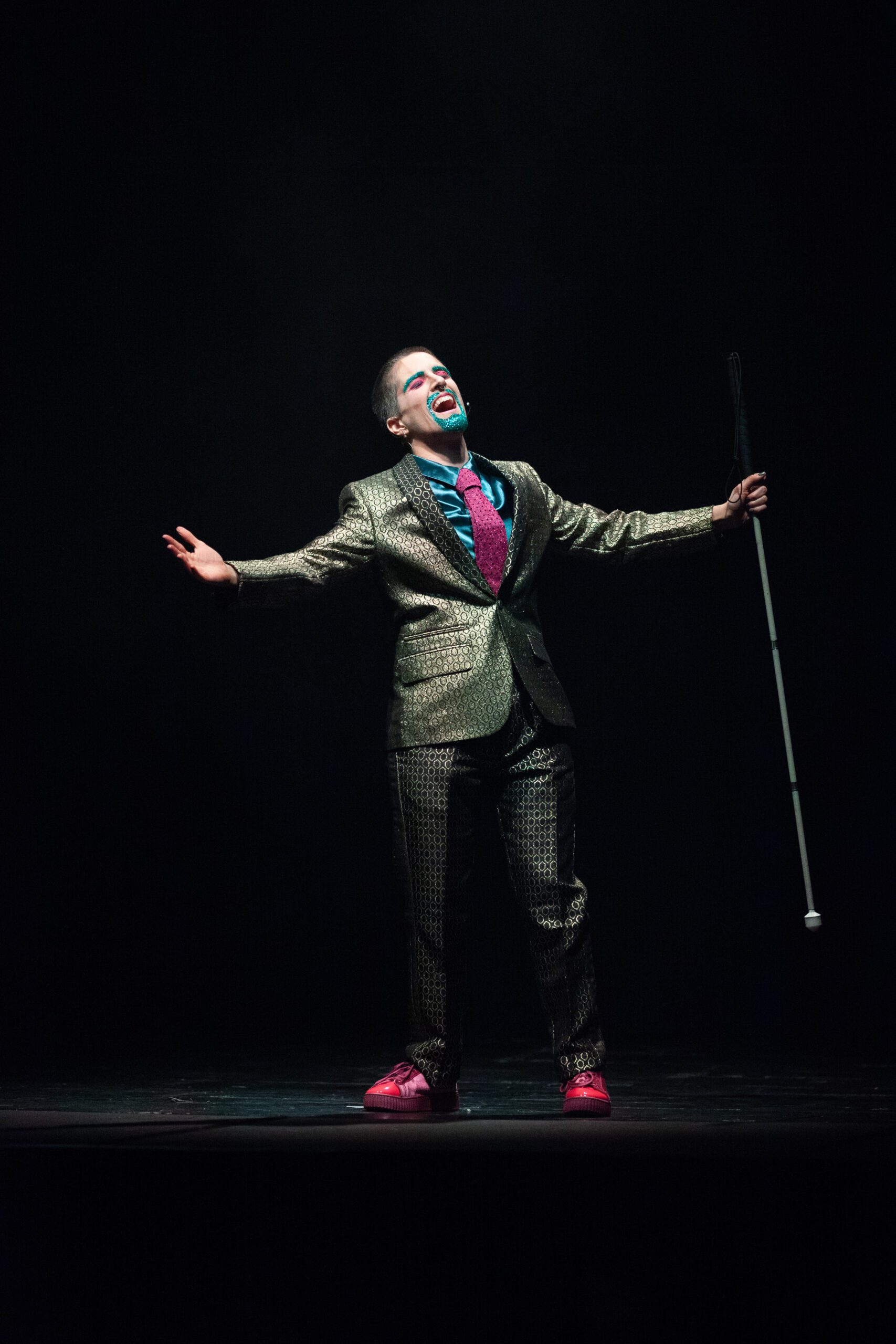 A slim white drag king in a suit and sparkly beard open their arms wide on a dark stage