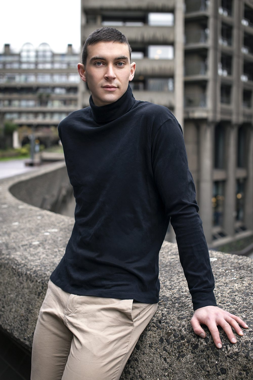 mid-shot of a man leaning on a stone wall outdoors in a navy turtleneck