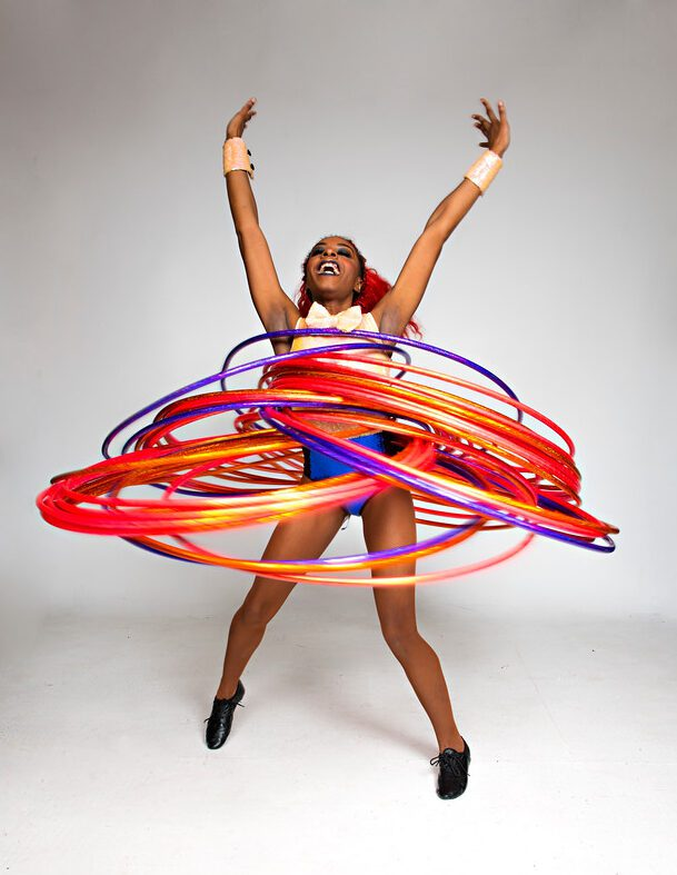 A black woman stands in a white room, spinning lots of hula hoops around her body
