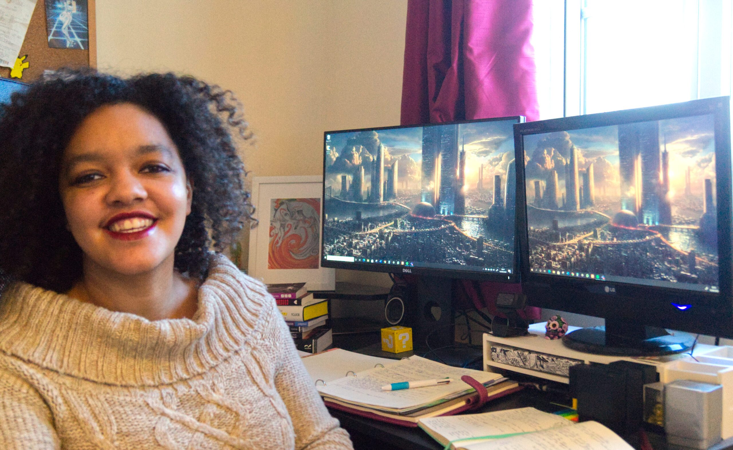 A mixed race woman sits in front of two computer screens, smiling.