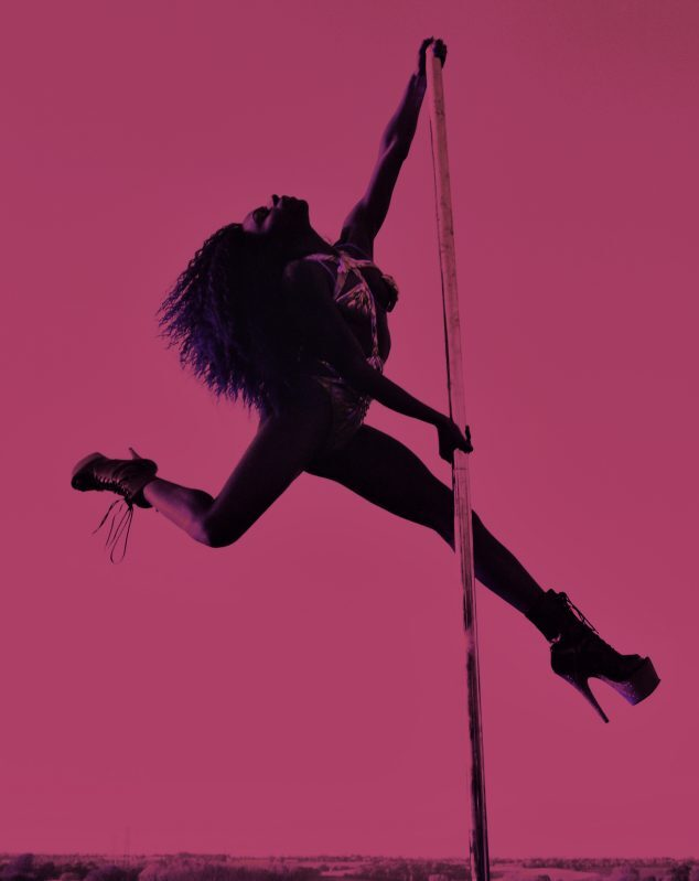 A woman wearing stilettos swings from a pole on a bright pink background.