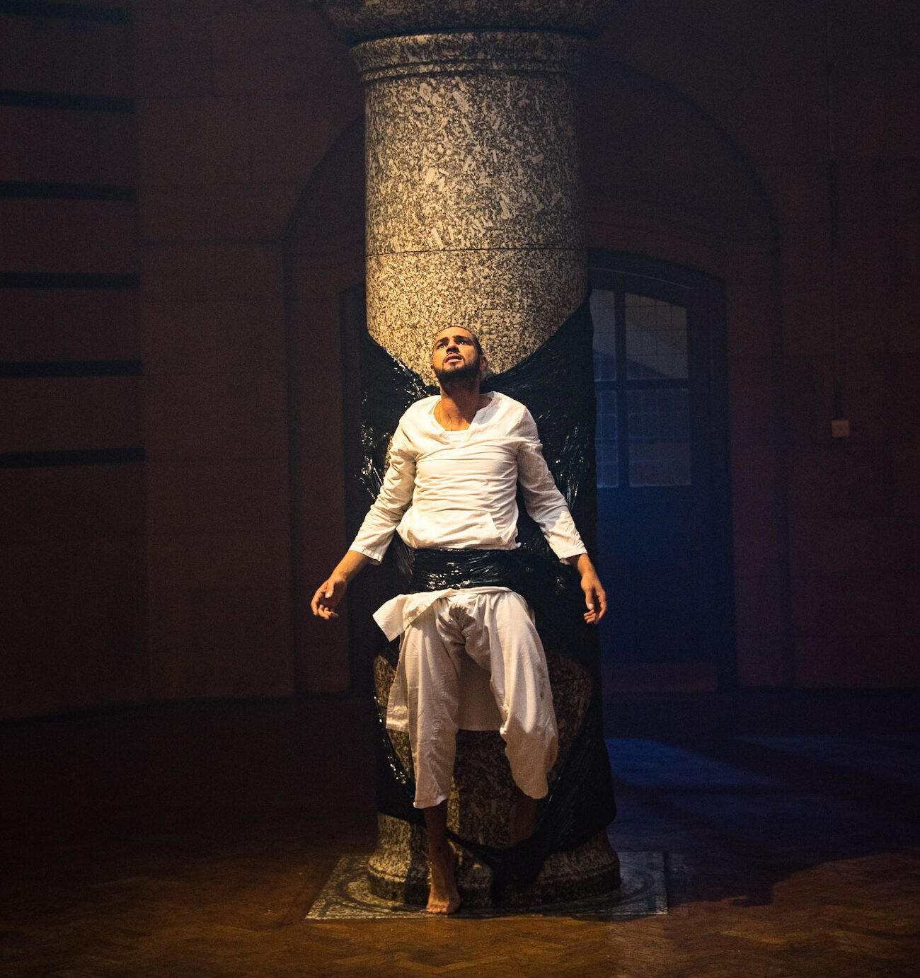 A man wearing white clothes is duct-taped to a large stone pillar