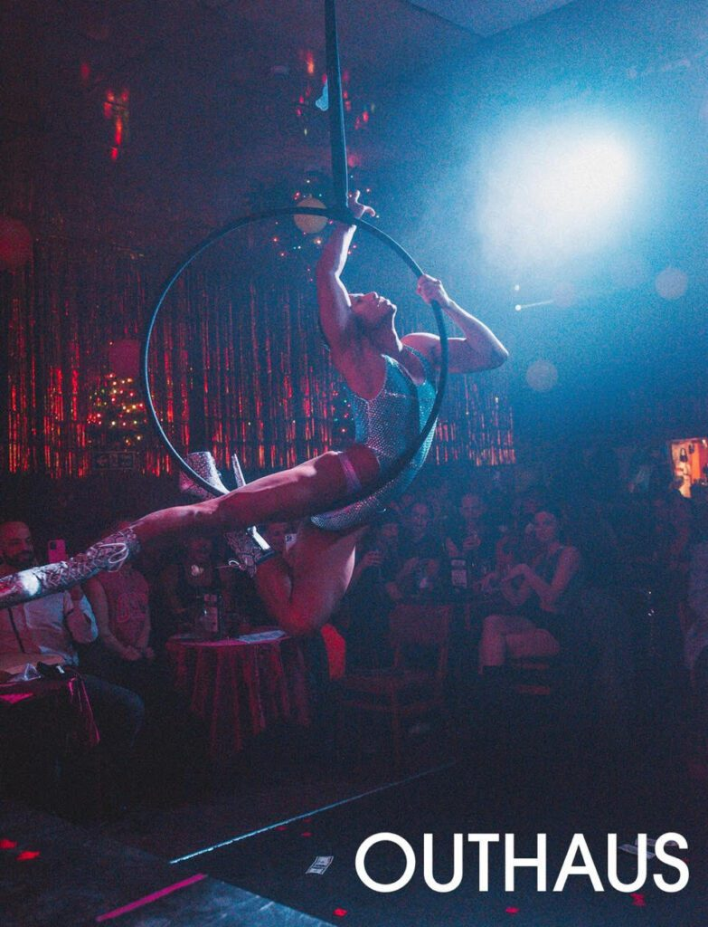 A performer balances on an aerial hoop under a bright spotlight on stage.
