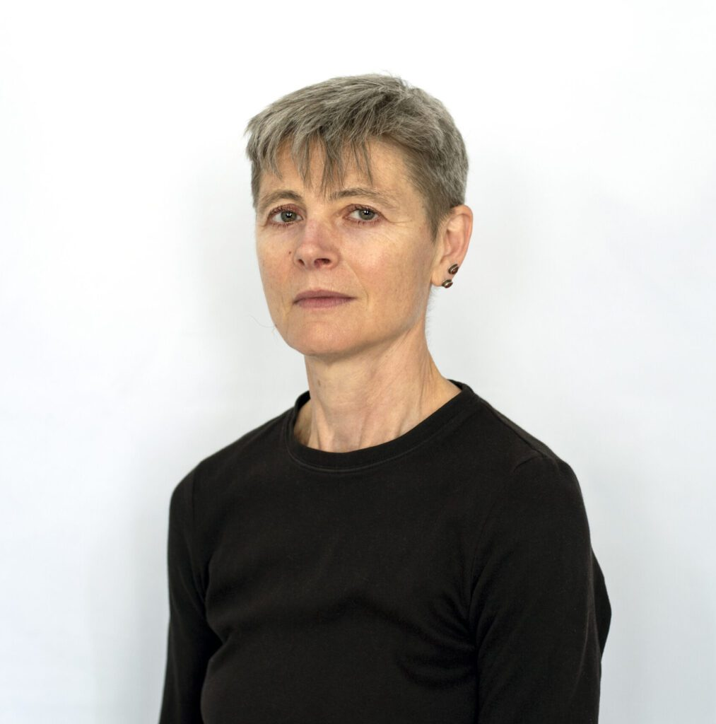 A mid shot of a woman with grey hair standing in front of a white wall in a black top