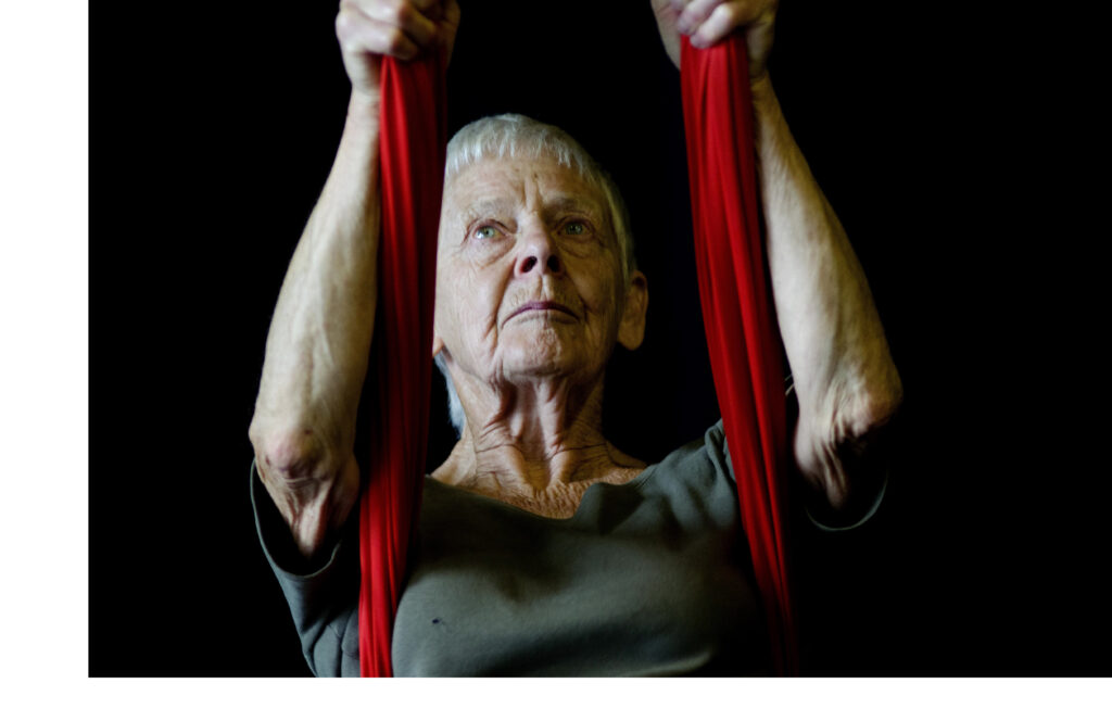 An elderly white woman with short grey hair is holding onto two aerial ropes.